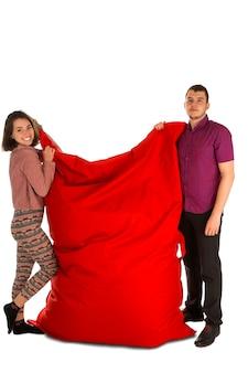 居間または白で隔離された他の部屋のための赤い長方形のビーンバッグソファチェアを立って保持している若い女性と男性
