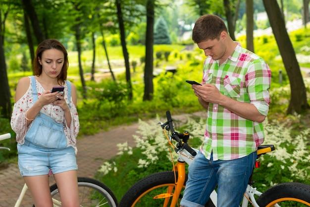 公園や森で自転車に寄りかかってスマートフォンでインターネットサーフィンをしている若い女性と男性