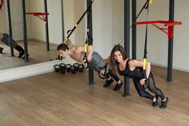 Тренировочные упражнения молодой женщины и мужчины отжимаются с ремнями фитнеса trx в тренажерном зале концепция здорового образа жизни разминки.