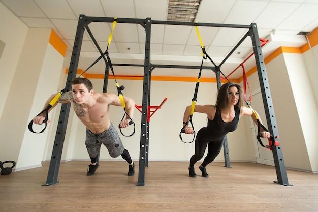 若い女性と男性のトレーニング運動はジムでtrxフィットネスストラップで腕立て伏せ
