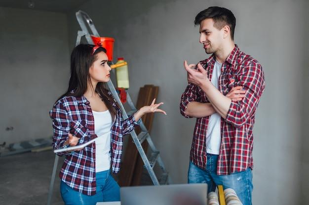 新しいことを教えている間アパートの改修中に論争している若い女性と男性