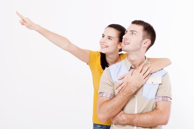 젊은 여자와 여름 의류에 흰색 완벽한 미소를 가진 남자는 흰 벽에 빈 공간에 옆으로 포인트 앞 손가락을 보여줍니다.