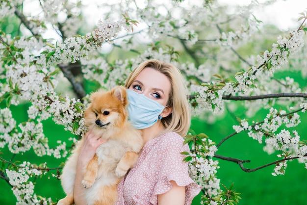 Молодая женщина и красный шпиц с медицинской маской на лице на природе в весенний день. коронавирус пандемия