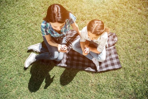 Молодая женщина и маленький ребенок сидели на одеяле и держат минусы мороженого.