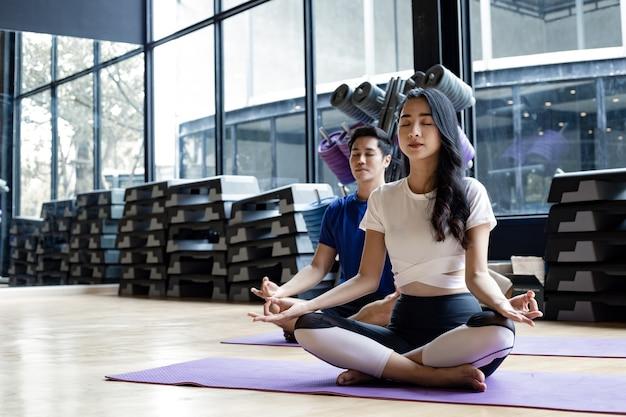 Молодая женщина и молодой человек, сидя медитации, занимаясь йогой на коврике для йоги в тренажерном зале с копией пространства. молодые пары с упражнениями, вместе занимаясь йогой в помещении. концепция упражнений с йогой.
