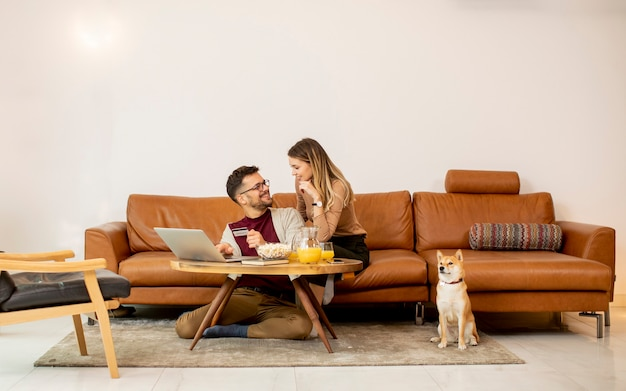 Молодая женщина и молодой человек используют ноутбук для онлайн-платежей, сидя на диване со своей собакой шиба-ину дома