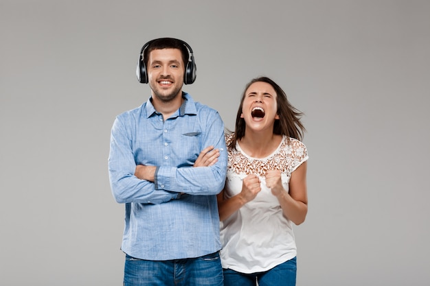 Young woman angering with man in headphones over grey wall