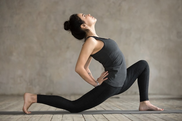 Young woman in anjaneyasana pose