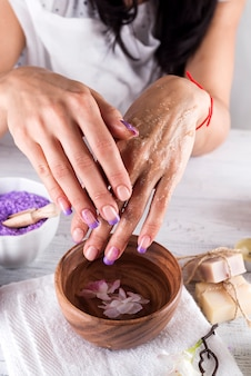 Young woman applies a coffee scrub on hands