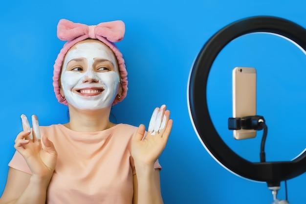 젊은 여자가 그녀의 얼굴에 크림 화장품 마스크를 적용하고 그녀의 스마트 폰에서 온라인으로 친구와 의사 소통합니다.