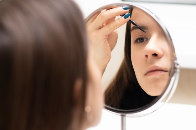 A young woman applies makeup while looking in the mirror