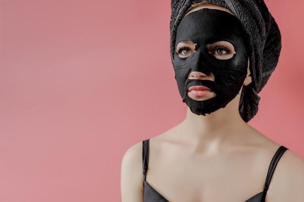 若い女性はピンクの背景に黒の化粧品生地の顔のマスクを適用します。フェイスピーリングマスク、チャコール、スパビューティートリートメント、スキンケア、美容。閉じる