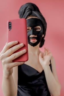 Young woman apply black cosmetic fabric facial mask and phone in hands . face peeling mask with charcoal, spa beauty treatment, skincare, cosmetology. close up