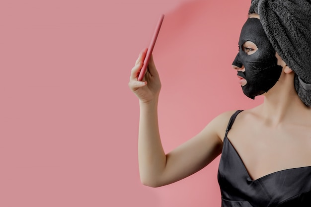 Young woman apply black cosmetic fabric facial mask and phone in hands on pink wall. face peeling mask with charcoal, spa beauty treatment, skincare, cosmetology. close up