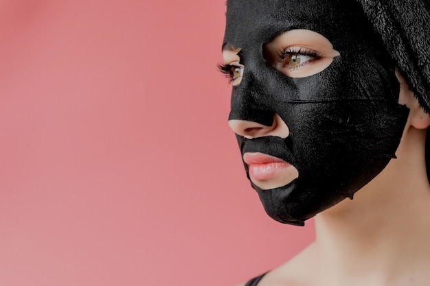 Young woman apply black cosmetic fabric facial mask on pink background. face peeling mask with charcoal, spa beauty treatment, skincare, cosmetology. close up