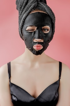 Young woman apply black cosmetic fabric facial mask on pink wall. face peeling mask with charcoal, spa beauty treatment, skincare, cosmetology. close up