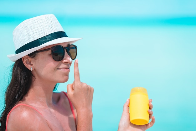 Young woman apply cream on her nose at beach