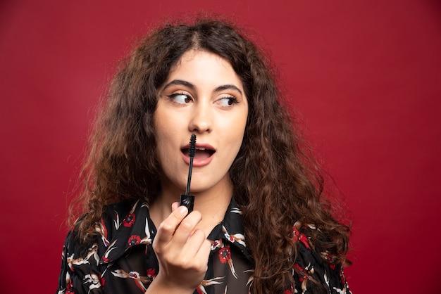 赤い壁にマスカラを適用する若い女性。
