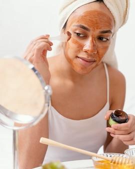 자연 얼굴 마스크를 적용하는 젊은 여자