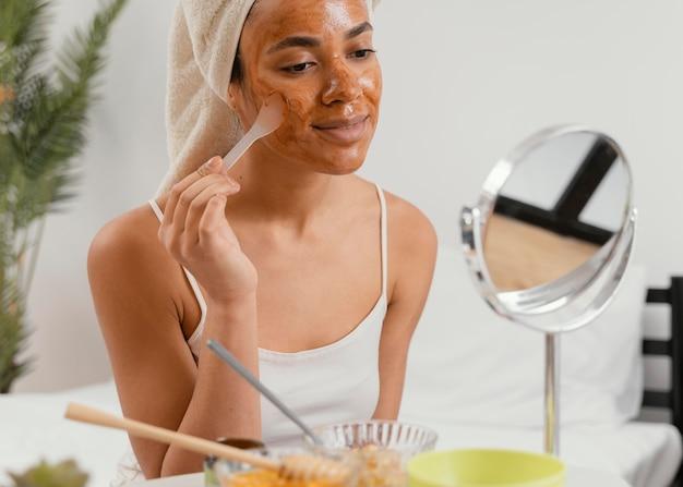Молодая женщина, применяя естественную маску для лица