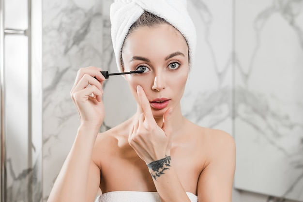 Young woman applying black mascara on eyelashes with brush wrapped in towels in the bathroom
