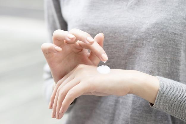 Молодая женщина, применяющая крем для тела дома