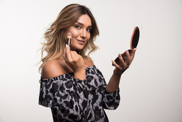 Young woman applying bronzer on white wall.
