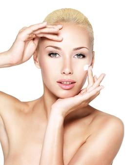 Giovane donna che applica crema cosmetica su un viso fresco e pulito
