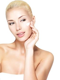 깨끗하고 신선한 얼굴에 화장품 크림을 적용하는 젊은 여자