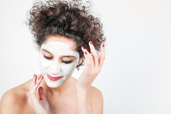 Young woman applying cosmetic cream on her face against white background