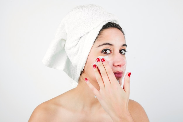 Young woman applying cream on face with white towel over her head