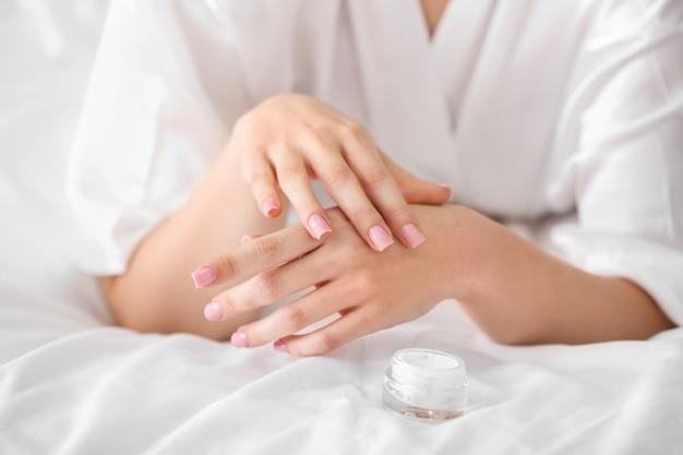 Молодая женщина, применяя крем на коже дома, крупным планом