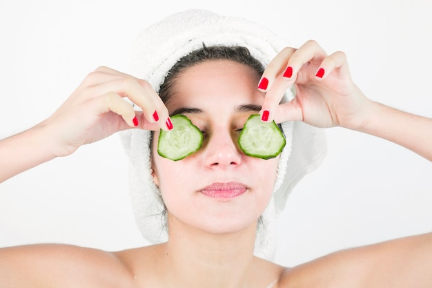 Young woman applying cucumber slices over her eyes against white background