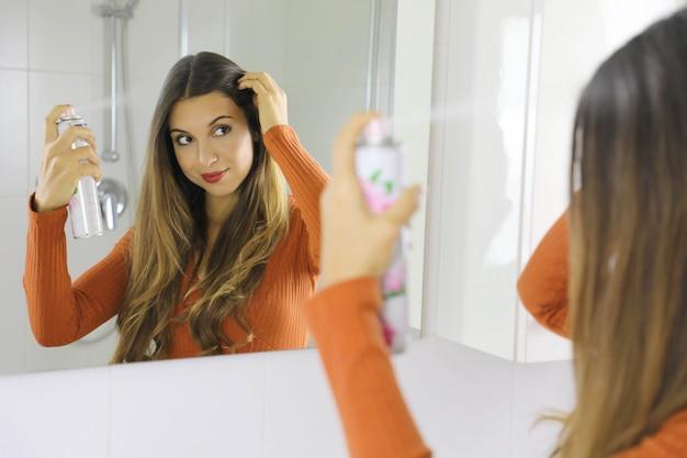 Молодая женщина, наносящая сухой шампунь на волосы