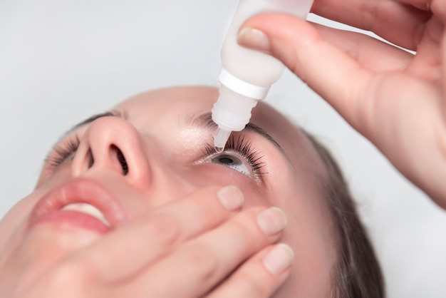 Young woman applying eye drops.