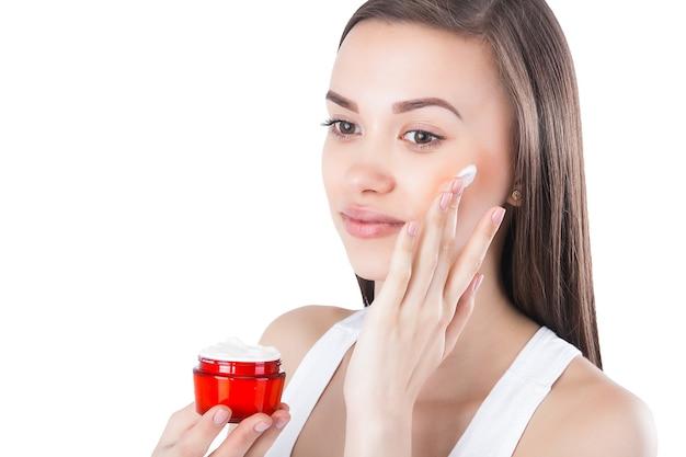 Молодая женщина, применяя крем для лица. крем для разглаживания лица. баночка с увлажняющим кремом.