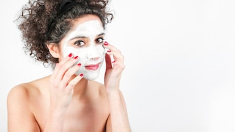 Young woman applying facial cosmetic mask on white background
