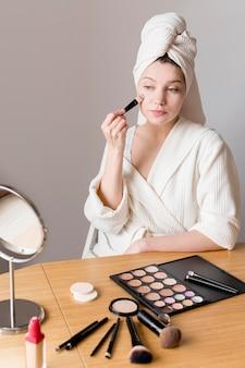 鏡にファンデーションを適用する若い女性