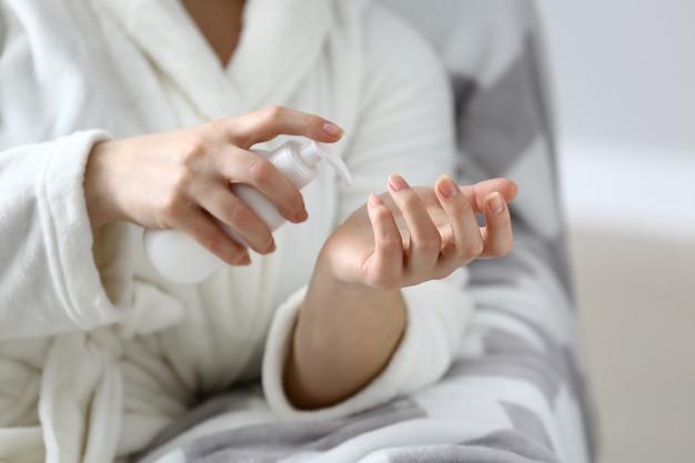 Молодая женщина, применяя крем для рук, крупным планом