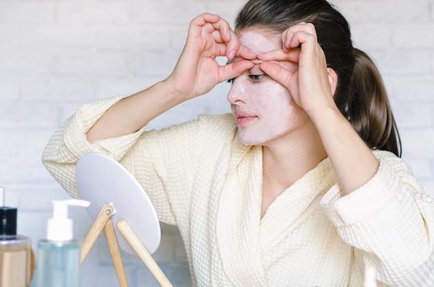 リフティングマスクを適用し、顔のセルフマッサージを行う若い女性 Premium写真