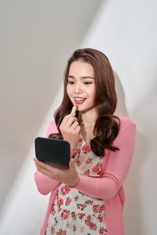 化粧筆で唇メイクをする若い女性