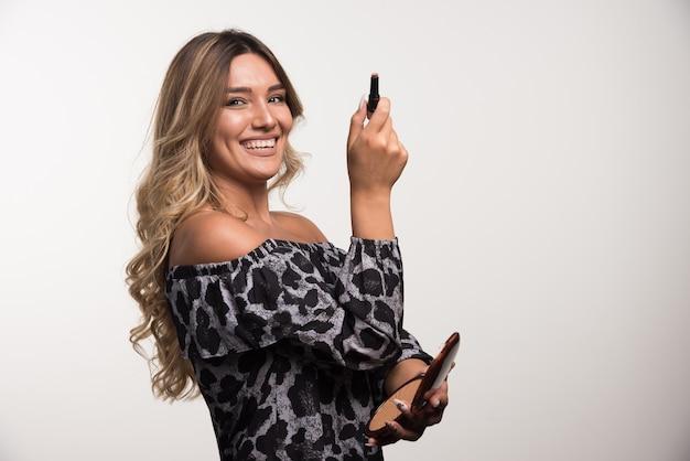 Giovane donna che applica rossetto sulla parete bianca.