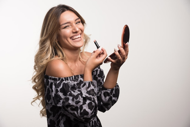 Young woman applying lipstick with happy expression.