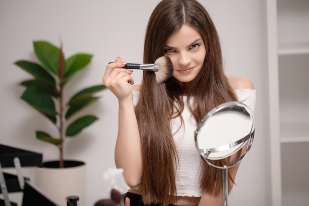 Young woman applying makeup on face at home.