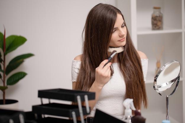 Молодая женщина, применяя макияж на лице дома.