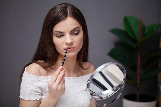 Молодая женщина, применяя косметику на лице у себя дома.