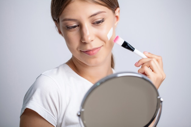 Young woman applying moisturizer on her face in front of mirror