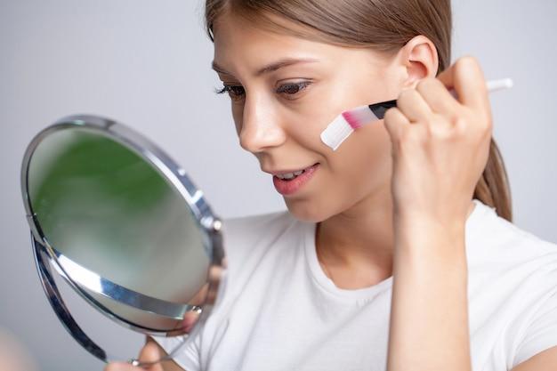 Молодая женщина, наносящая увлажняющий крем на лицо перед зеркалом