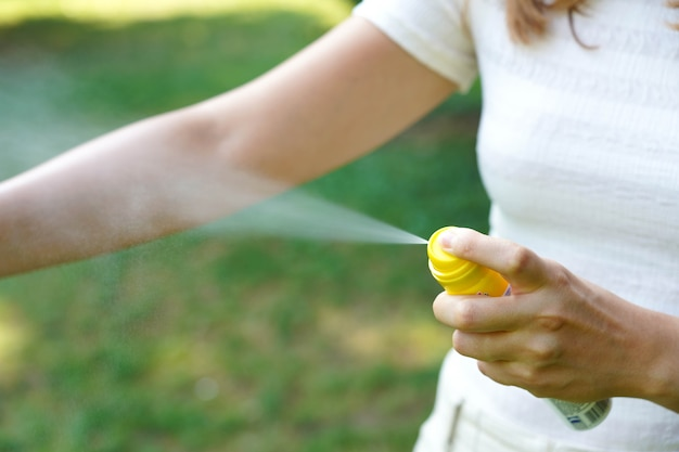 自然の中でのハイキング中に彼女の腕に蚊忌避剤を適用する若い女性。防虫剤。ダニや他の昆虫に対する皮膚の保護。スプレー容器の上部に焦点を合わせます。