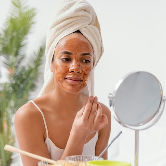 Young woman applying a natural face mask